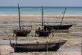 Dhow traditional sailing vessels beached waiting for an incoming awaiting tide seen on a sunny day with bright ocean backdrop Stock Photos