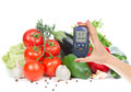 Diabetes concept glucose meter in hand and healthy organic food vegetables green avocado tomatoes cucumbers salad pepper on a Stock Photography