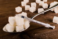 Diabetes. A lot of sugar cubes in spoon and injector