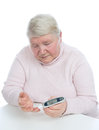 Diabetes senior woman measuring glucose level blood test patient with glucometer and small drop of on a white background Royalty Free Stock Photo