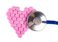 Diagnose closeup view of blue stethoscope on a heart shaped pills Royalty Free Stock Photography