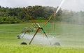Diagonal center pivot irrigatio system a shot of a irrigation in green fields with forest and luxury home in the background Stock Image