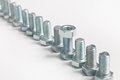 Diagonal row of bolts with a single nut Royalty Free Stock Photo