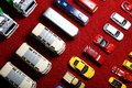 Diagonal rows of toy cars four the used and some broken colorful on the red carpet Royalty Free Stock Photos