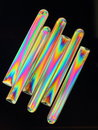 Diagonal tubes six small of transparent plastic arranged diagonally used as brandy glasses seen through polarized light on black Stock Photo