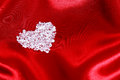 Diamond heart on red satin Stock Photos