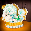 Diaper snail cake diapers rolled up to create a with baby clothes and ribbon Royalty Free Stock Photography