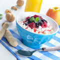 Diary breakfast with fruits cottage cheese in blue bowl raspberries blueberries and mint Stock Photography