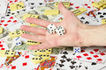 Dice on palm on the background cards and money Royalty Free Stock Photo