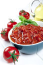 Diced tomatoes and whole with olive oil behind garnished with basil Stock Photo