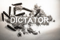 Dictator word written in  ash, dirt, dust with bullets around as Royalty Free Stock Photo