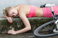 Died for sport exhausted girl laying on the ground after bicycle race Stock Photo