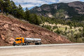 Diesel semi trailer truck on highway in rocky mountains orange transporting fuel down a the Royalty Free Stock Image