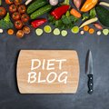 Diet blog concept. Vegetables, empty wooden cutting board and chef`s knife on a black background Royalty Free Stock Photo