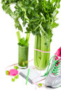 Diet concept with a celery sports shoes notebook pencil and fresh glass juice on white planning of Stock Images