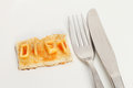 Diet concept small piece of toast with spelt using alphabet spaghetti with a knife and fork on a plate Stock Photo