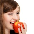 Diet girl eating biting apple seasonal fruit and nutrition happy young woman isolated on white recommending healthy lifestyle Stock Photo