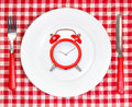 Diet lunch  time concept.Red alarm clock on round white plate. Royalty Free Stock Photo