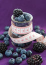 Diet meal blackberry and blueberry in a glass jar with measure tape on the purple background top view Stock Image