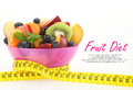 Diet meal fruit salad in a bowl with measuring tape on white background Stock Images
