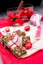 Diet muesli bars with detox apple cinnamon water and measuring tape on red pepper and wooden background Royalty Free Stock Photo
