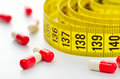 Diet pills and measuring tape Royalty Free Stock Photos