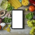 diet plannig. Set of raw food with tablet on wooden background with gadget screen with copy space. Healthy food concept, top view Royalty Free Stock Photo