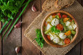 Diet vegetable soup with chicken meatballs and fresh herbs in wooden bowl, top view. Royalty Free Stock Photo