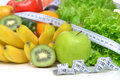 Diet weight loss breakfast concept with tape measure organic gre green apple salad bananas kiwi avocado grapefruit red pepper pear Royalty Free Stock Photos