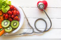 Diet and weight loss for healthy care with medical stethoscope, with red heart and fresh vegetable salad and healthy food on woode Royalty Free Stock Photo