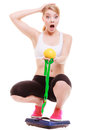Diet weightloss. Surprised woman on scale holds fruit measuring tape Royalty Free Stock Photo