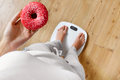 Diet. Woman On Weighing Scale, Holding Donut. Unhealthy Food. Ob Royalty Free Stock Photo