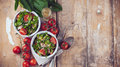 Dietary food background vegetable salad with spinach cherry tomatoes barley porridge and olive oil on an old wooden board vegan Royalty Free Stock Images