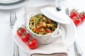 Dietary pasta with spinach zucchini and cherry tomatoes in a white ceramic pot on served table fresh homemade lunch Stock Images