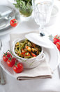 Dietary pasta with spinach zucchini and cherry tomatoes in a white ceramic pot on served table fresh homemade lunch Royalty Free Stock Photos