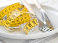 Dieting concept with fork knife and meter selective focus Stock Photo