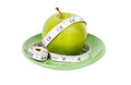 Dieting concept Green apple with measuring tape Stock Photos