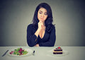 Dieting concept, woman choosing between healthy food and tasty cake Royalty Free Stock Photo