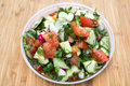 Dieting healthy salad on rustic wooden table top view mixed greens tomatos cucumber olive oil and spices for lifestyle Stock Photos