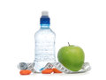 Dietting breakfast diabetes weight loss concept with tape measure organic green apple bottle of drinking water and dried apricots Royalty Free Stock Image