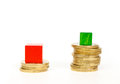 Difference in mortgage payments shown stacks of coins and wooden cubes Royalty Free Stock Photo