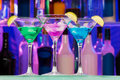 Different alcohol color drinks with lime cocktail in the glasses and bottles on the bar shelf Stock Photo