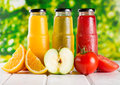 Different bottles of juice with fruits on wooden table Stock Photography