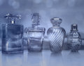 Different bottles of perfume on blue background. Royalty Free Stock Photo