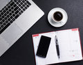 Different business objects on a black table background composition of coffee laptop diary and mobile phone the image is taken Royalty Free Stock Photo