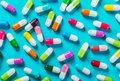 Different color pills on blue background Royalty Free Stock Photo