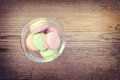 Different colors and flavors french macarons on old wooden background Stock Images