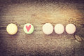 Different colors and flavors french macarons on old wooden background hidden text i love you Stock Image