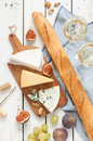 Different kinds of cheeses baguette wine figs and grapes brie parmesan blue cheese two glasses white white wooden table as Stock Images