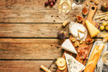 Different kinds of cheeses wine baguettes fruits and snacks on rustic wooden table from above french tasting party or feast Stock Photo
